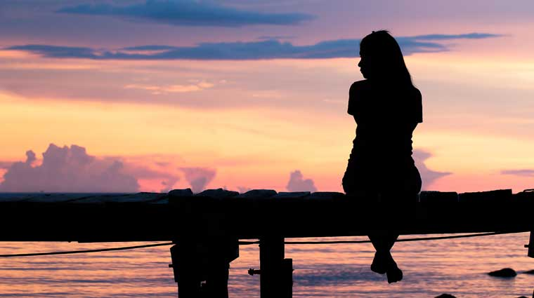 girl sitting on a dock at sunset